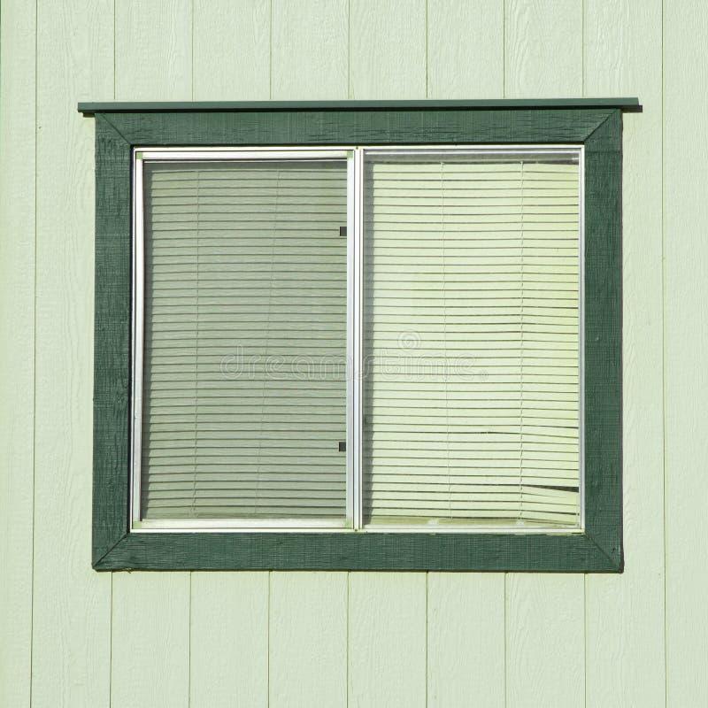 Παλαιό παράθυρο με τους πλαστικούς τυφλούς παραθύρων με τους ξύλινους τοίχους στοκ εικόνα