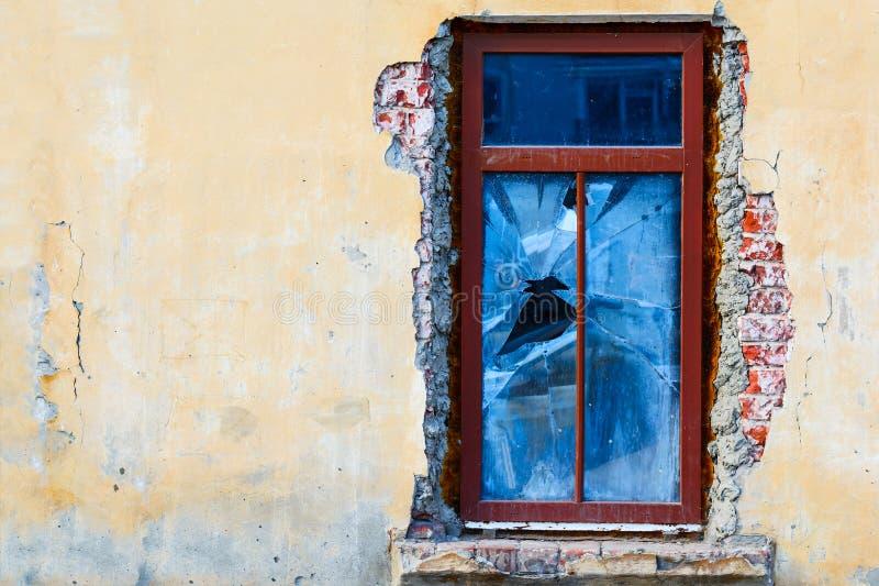 Παλαιό παράθυρο συντριβής σε ένα εγκαταλειμμένο παλαιό κτήριο Σπασμένο παράθυρο στον κίτρινο τοίχο Παλαιός και βρώμικος τοίχος το στοκ εικόνα