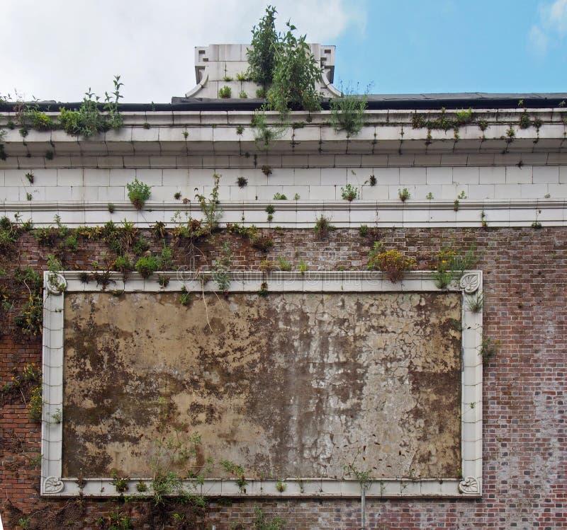 Παλαιό πλαίσιο αφισών πετρών στον τοίχο ενός εγκαταλελειμμένου κινηματογράφου με τις εγκαταστάσεις που αυξάνονται από έναν αποσυν στοκ φωτογραφίες με δικαίωμα ελεύθερης χρήσης