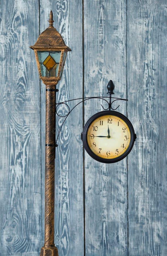 Παλαιό ρολόι σε έναν πόλο με ένα φανάρι Σε ένα ξύλινο γκρίζο υπόβαθρο στοκ φωτογραφία