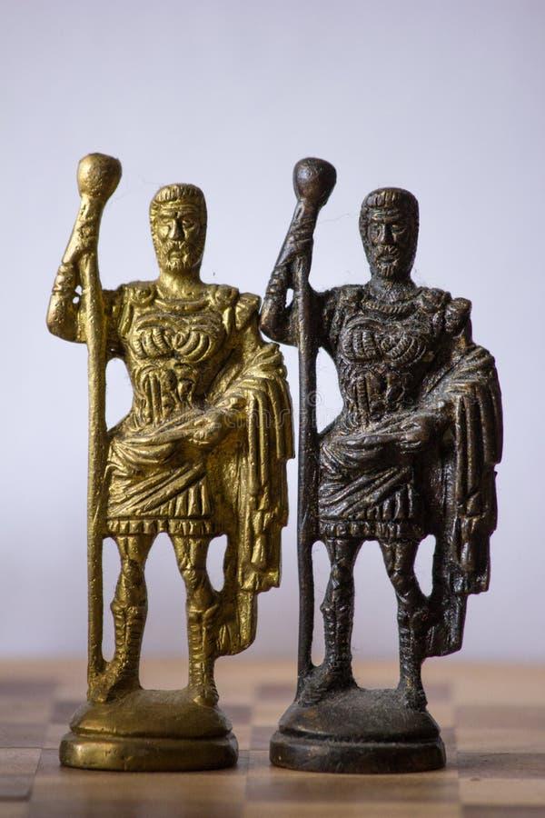 Παλαιό σκάκι με τα καλλιτεχνικά κομμάτια βασιλιάδων ορείχαλκου που στέκονται από κοινού στοκ εικόνες