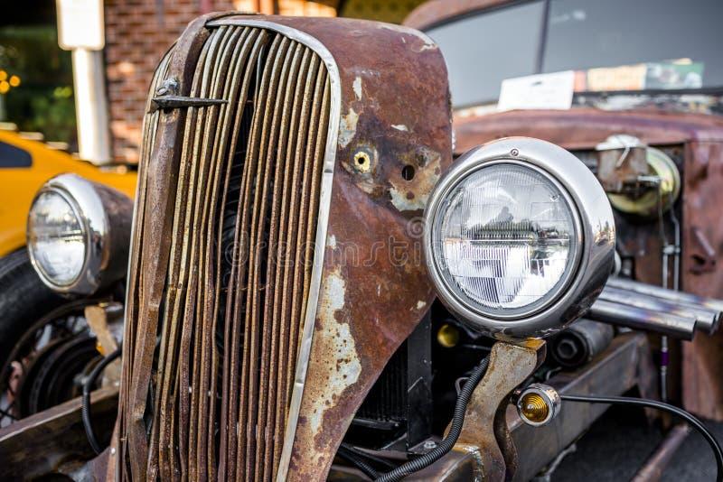 Παλαιό σκουριασμένο αυτοκίνητο που δουλεύει με παλιρροϊκό αυτοκίνητο με λυγαριά και νέο προβολέα που στέκεται σε έκθεση σε δρόμο  στοκ φωτογραφία