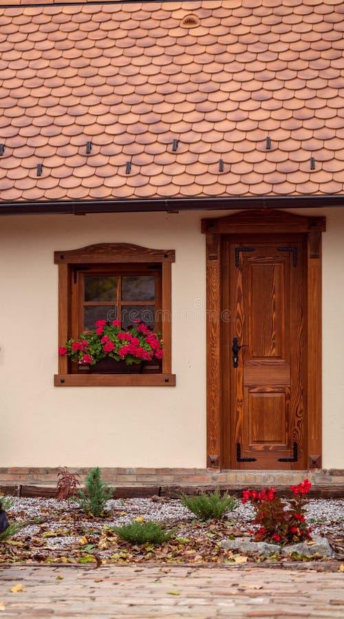 Παλαιό σπίτι με τα παράθυρα και τα λουλούδια, ξύλινες πόρτες, εγκαταστάσεις στοκ εικόνες