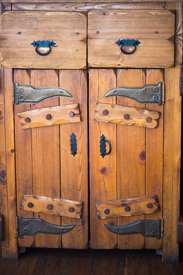 Παλαιό στερεό ξύλινο γραφείο με τις πόρτες και τα συρτάρια Μαύρες σφυρηλατημένες μέταλλο συναρμολογήσεις στοκ εικόνες