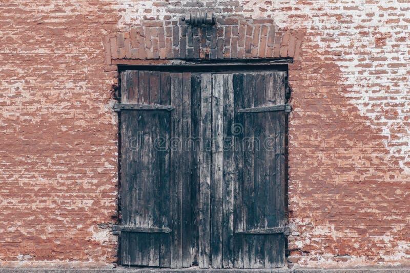 Παλαιό τούβλινο υπόβαθρο σύστασης τοίχων αστικό και ξύλινη πόρτα στοκ εικόνες
