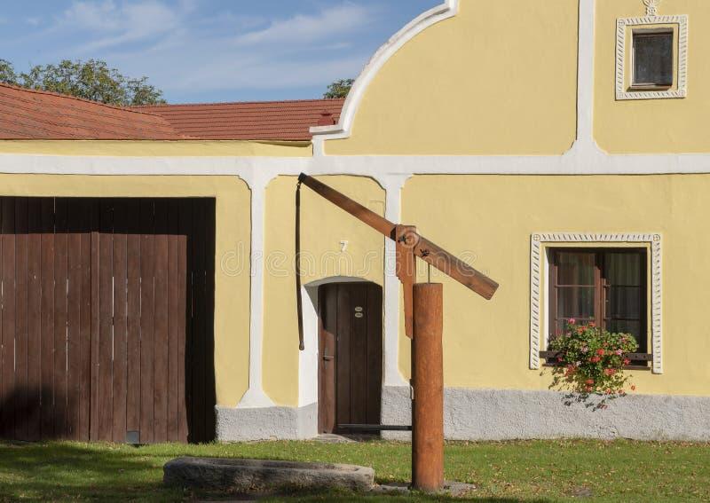 Παλαιό φρεάτιο νερού μπροστά από το σπίτι, το χωριό Holasovice, Δημοκρατία της Τσεχίας στοκ εικόνες με δικαίωμα ελεύθερης χρήσης