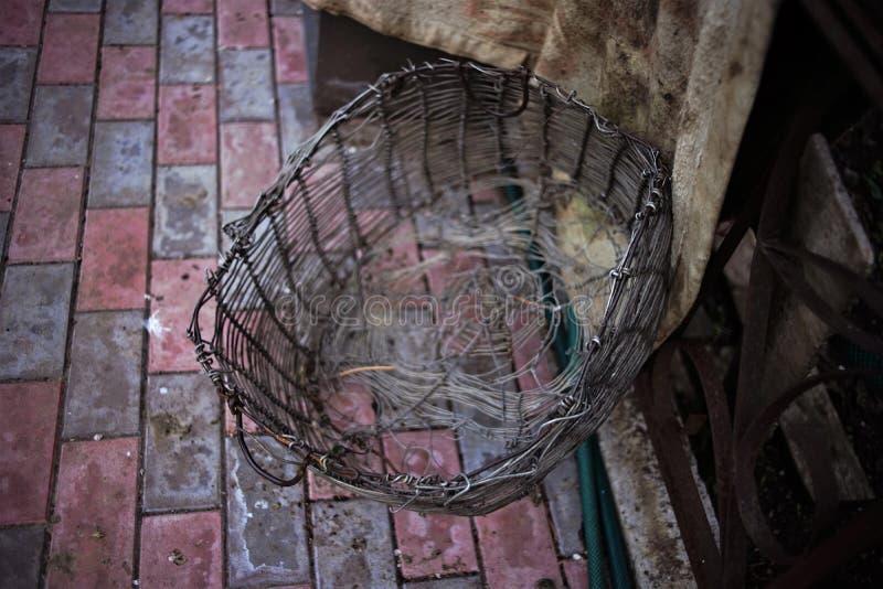Παλαιό ψάθινο καλάθι φιαγμένο από πλέγμα αργιλίου σε ένα κεραμωμένο πάτωμα στοκ εικόνες