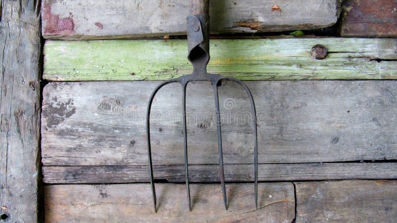 Παλαιό pitchfork σε μια ξύλινη επιφάνεια γεωργικά εργαλεία στοκ εικόνες