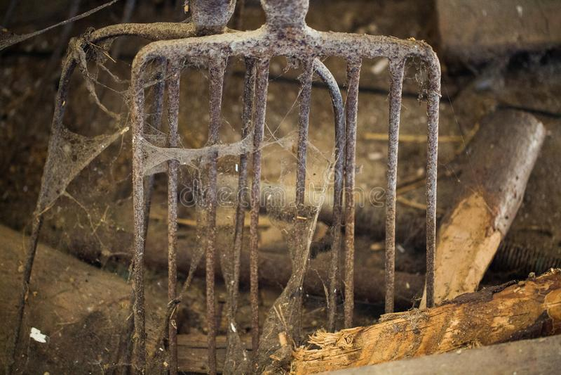 Παλαιό pitchfork στο σταύλο με τους ιστούς αράχνης στοκ φωτογραφίες
