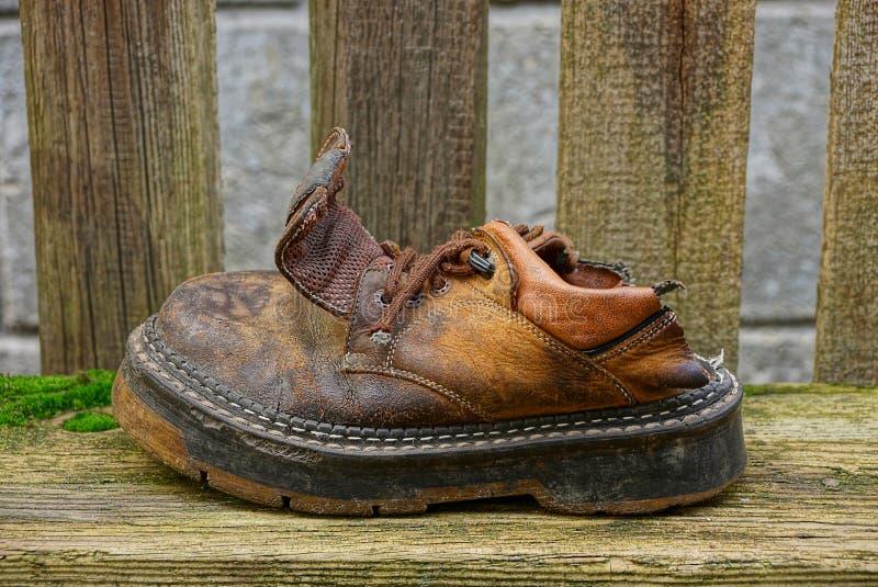 Παλαιό ragged καφετί παπούτσι σε έναν γκρίζο πίνακα στοκ φωτογραφία με δικαίωμα ελεύθερης χρήσης