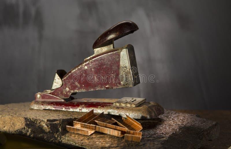 Παλαιό stapler στην πέτρα και το σκοτεινό υπόβαθρο στοκ εικόνες