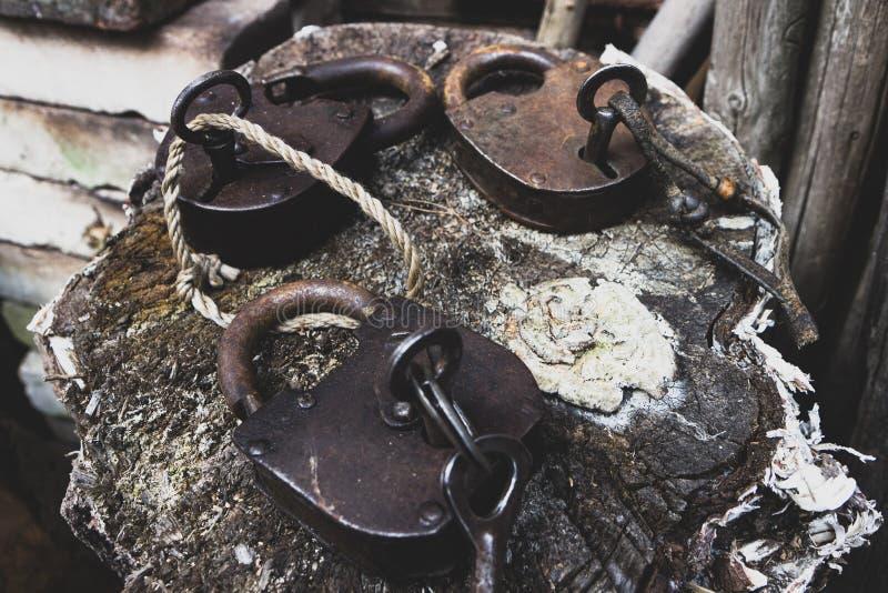 Παλιός δρομέας γρύλος ανοιχτός και κλειδωμένος λουκέτος κλεισμένος σε ξύλινο φόντο στοκ εικόνα