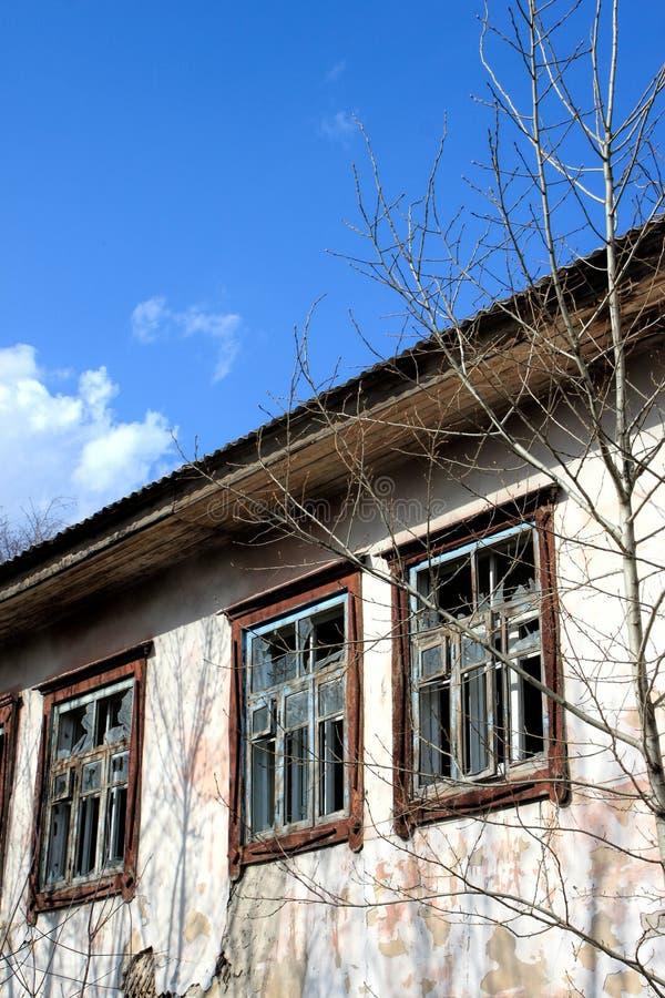 Παλιό εγκαταλελειμμένο κτίριο - άδεια παράθυρα με σπασμένα γυαλιά στοκ εικόνα