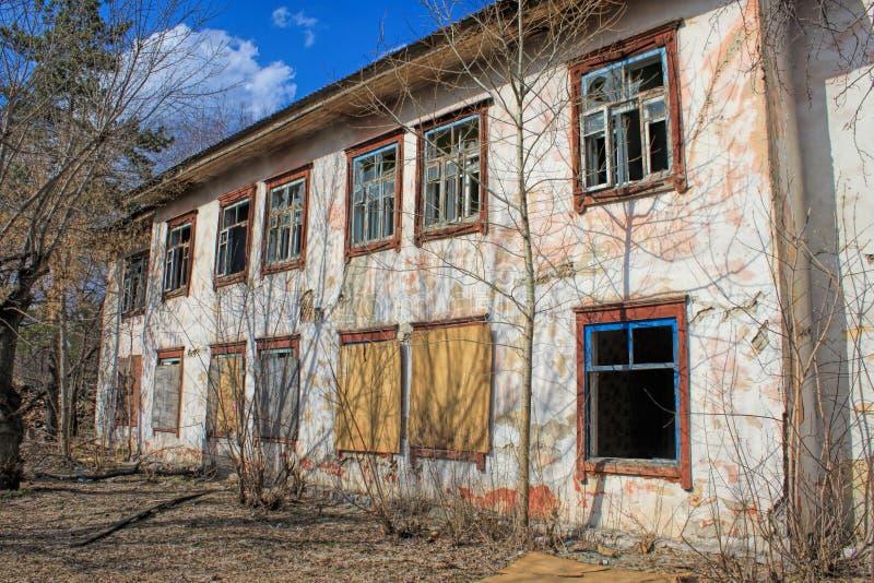 Παλιό εγκαταλελειμμένο κτίριο - άδεια παράθυρα με σπασμένα γυαλιά στοκ φωτογραφία