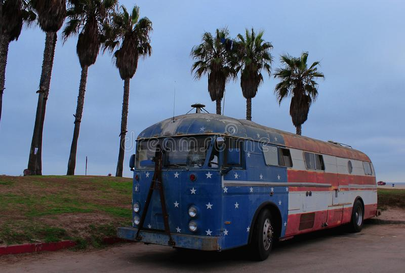 Παλιό σχολικό λεωφορείο με το χρώμα της σημαίας των Ηνωμένων Πολιτειών της Αμερικής στην ακτή στη Σάντα Μόνικα στοκ εικόνες με δικαίωμα ελεύθερης χρήσης