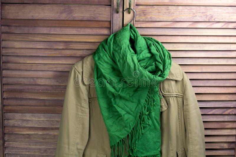Παλτό με το μαντίλι στην κρεμάστρα στοκ εικόνα με δικαίωμα ελεύθερης χρήσης