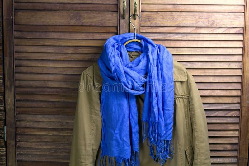 Παλτό με το μαντίλι στην κρεμάστρα στοκ φωτογραφία