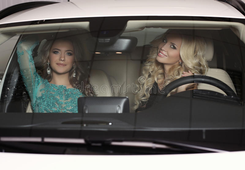Πανέμορφες γυναίκες με τα μακρυμάλλη πολυτελή φορέματα ένδυσης, που θέτουν στο αυτοκίνητο στοκ εικόνες