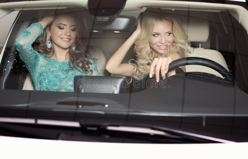 Πανέμορφες γυναίκες με τα μακρυμάλλη πολυτελή φορέματα ένδυσης, που θέτουν στο αυτοκίνητο στοκ εικόνες με δικαίωμα ελεύθερης χρήσης