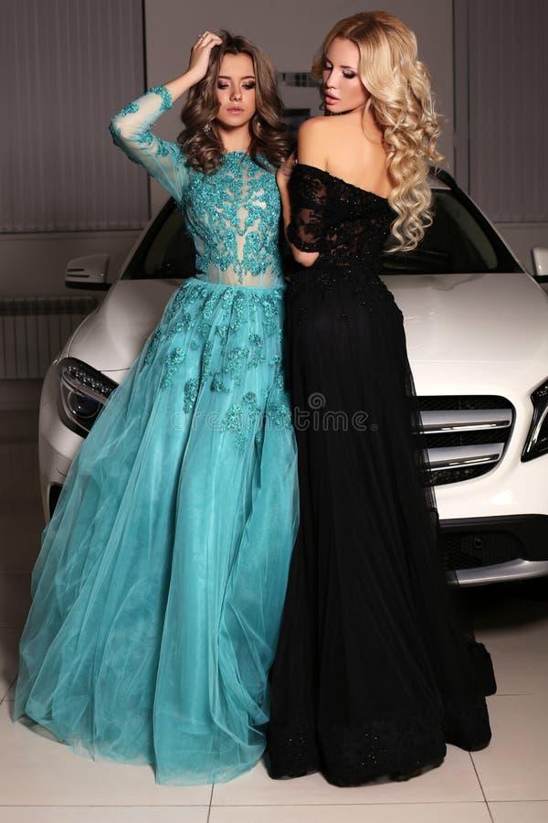 Πανέμορφες γυναίκες με τα μακρυμάλλη πολυτελή φορέματα ένδυσης, που θέτουν εκτός από το άσπρο αυτοκίνητο στοκ φωτογραφίες με δικαίωμα ελεύθερης χρήσης