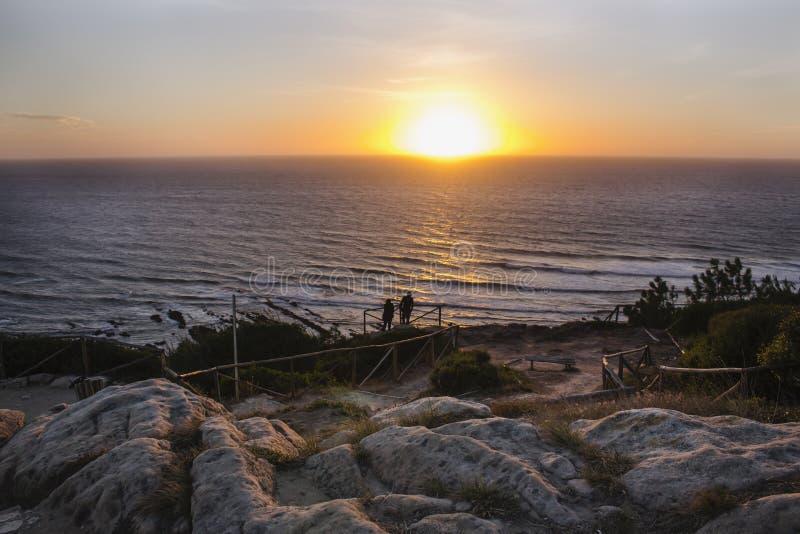 Πανέμορφη άποψη της θάλασσας με το δραματικό ηλιοβασίλεμα, που βλέπει από μια καλή και δύσκολη άποψη σε Cabo Mondego, στην Πορτογ στοκ φωτογραφία