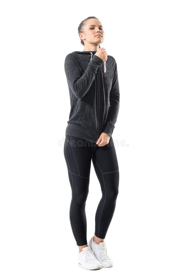 Πανέμορφη βέβαια φίλαθλη μπλούζα φερμουάρ γυναικών zipping με κουκούλα επάνω που εξετάζει τη κάμερα στοκ φωτογραφίες με δικαίωμα ελεύθερης χρήσης