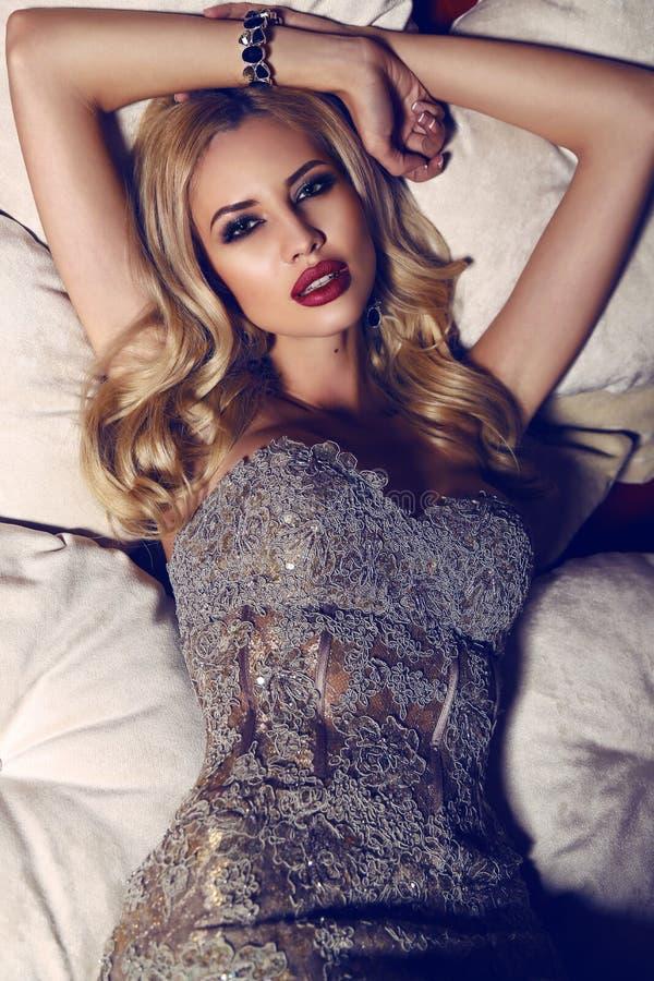 Πανέμορφη γυναίκα με τα ξανθά μαλλιά στο κομψό φόρεμα που βρίσκεται στο ντιβάνι στοκ εικόνες με δικαίωμα ελεύθερης χρήσης