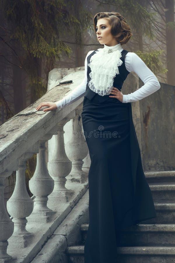 Πανέμορφη γυναίκα με το κομψό hairstyle που φορά την ντεμοντέ εσθήτα που στέκεται σε παλαιό τα βήματα στο κάστρο της στοκ εικόνα