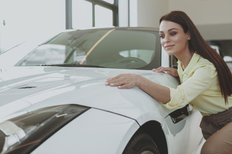 Πανέμορφη γυναίκα που αγοράζει το νέο αυτοκίνητο στον αντιπρόσωπο στοκ φωτογραφία