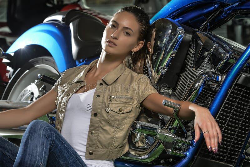 Πανέμορφη γυναίκα που κλίνει ενάντια στην μπλε μοτοσικλέτα της στοκ εικόνα