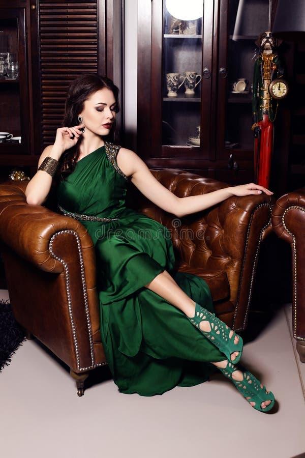 Πανέμορφη γυναίκα στην κομψή πράσινη τοποθέτηση φορεμάτων στο πολυτελές εσωτερικό στοκ εικόνες