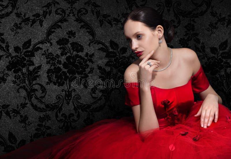 Πανέμορφη γυναίκα στο κόκκινο φόρεμα βραδιού στο Μαύρο στοκ εικόνες