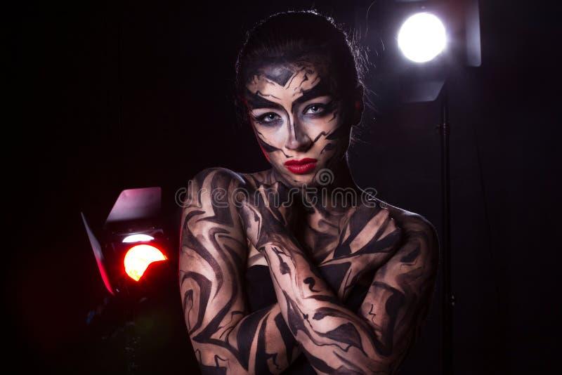 Πανέμορφη διακοσμημένη γυναίκα στην οποία τα επίκεντρα λάμπουν στοκ εικόνες