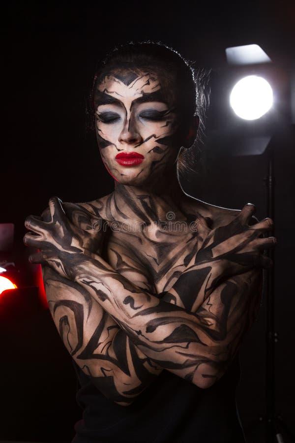 Πανέμορφη διακοσμημένη γυναίκα στην οποία τα επίκεντρα λάμπουν στοκ φωτογραφία με δικαίωμα ελεύθερης χρήσης