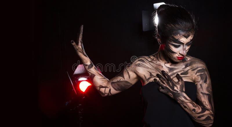 Πανέμορφη διακοσμημένη γυναίκα στην οποία τα επίκεντρα λάμπουν στοκ εικόνα με δικαίωμα ελεύθερης χρήσης