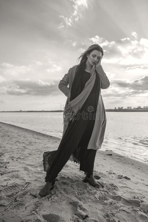 Πανέμορφη Ευρωπαία γυναίκα στο θερμό παλτό και φόρεμα σε έναν περίπατο στο πάρκο κοντά στον ποταμό Θυελλώδης καιρός Η μύγα ενδυμά στοκ φωτογραφία με δικαίωμα ελεύθερης χρήσης