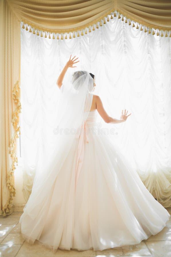 Πανέμορφη ευτυχής νύφη brunette πολυτέλειας κοντά σε ένα παράθυρο στο υπόβαθρο του εκλεκτής ποιότητας δωματίου στοκ φωτογραφίες με δικαίωμα ελεύθερης χρήσης