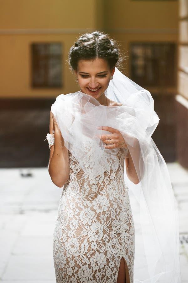 Πανέμορφη ευτυχής χαμογελώντας νύφη brunette στο εκλεκτής ποιότητας άσπρο φόρεμα pos στοκ εικόνα με δικαίωμα ελεύθερης χρήσης