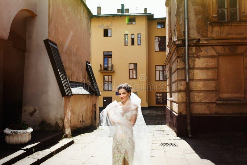 Πανέμορφη ευτυχής χαμογελώντας νύφη brunette στο εκλεκτής ποιότητας άσπρο φόρεμα pos στοκ εικόνα
