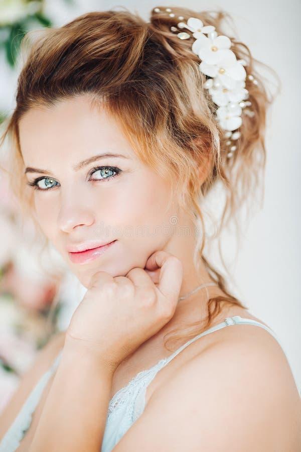 Πανέμορφη και όμορφη γυναίκα με το σγουρό hairstyle με τα λουλούδια στοκ εικόνες