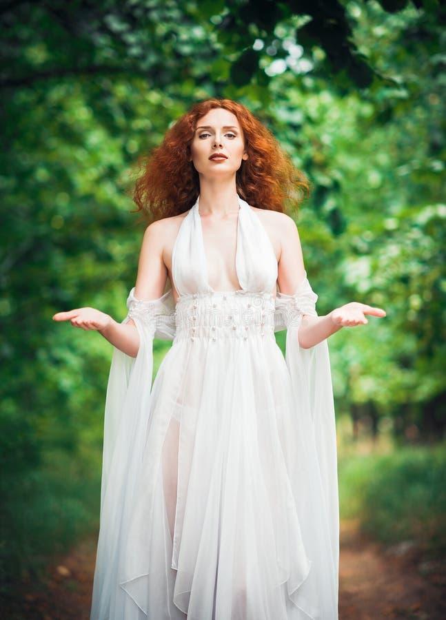 Πανέμορφη κοκκινομάλλης γυναίκα που φορά το άσπρο φόρεμα σε έναν κήπο στοκ εικόνες