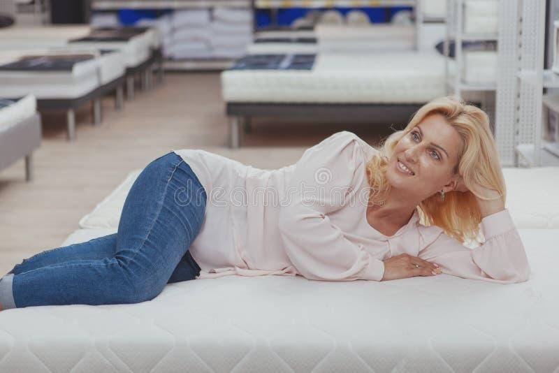Πανέμορφη κομψή ώριμη γυναίκα που ψωνίζει για το νέο ορθοπεδικό κρεβάτι στοκ φωτογραφία με δικαίωμα ελεύθερης χρήσης