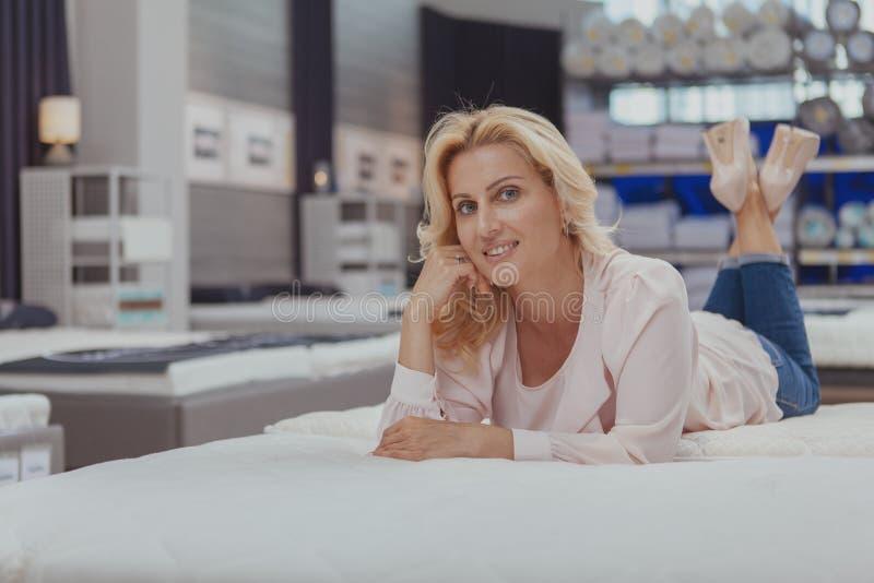 Πανέμορφη κομψή ώριμη γυναίκα που ψωνίζει για το νέο ορθοπεδικό κρεβάτι στοκ φωτογραφίες με δικαίωμα ελεύθερης χρήσης