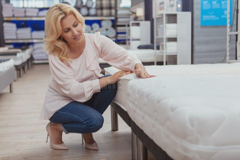 Πανέμορφη κομψή ώριμη γυναίκα που ψωνίζει για το νέο ορθοπεδικό κρεβάτι στοκ εικόνες