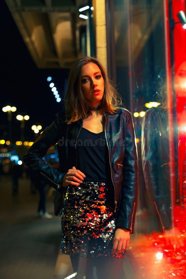 Πανέμορφη νέα γυναίκα που θέτει τη νύχτα την πόλη στοκ εικόνες