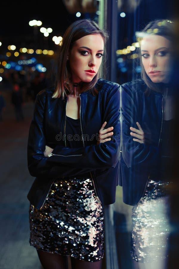 Πανέμορφη νέα γυναίκα που θέτει τη νύχτα την πόλη στοκ εικόνα