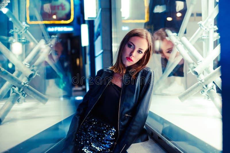 Πανέμορφη νέα γυναίκα που θέτει τη νύχτα την πόλη στοκ φωτογραφίες