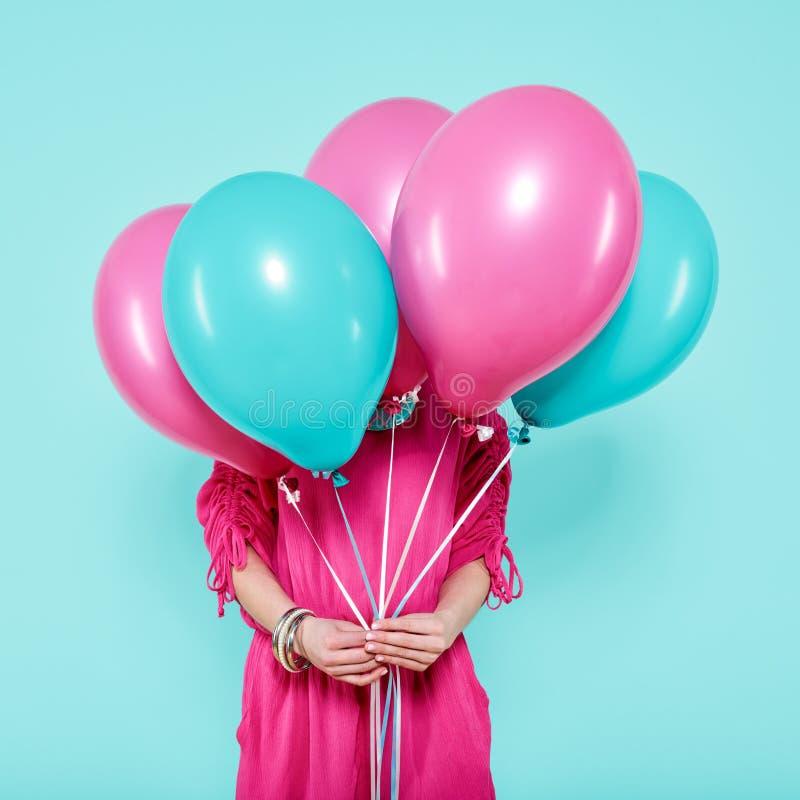Πανέμορφη νέα γυναίκα στη δέσμη εκμετάλλευσης εξαρτήσεων κομμάτων των ζωηρόχρωμων μπαλονιών, που απομονώνεται πέρα από το μπλε χρ στοκ εικόνα