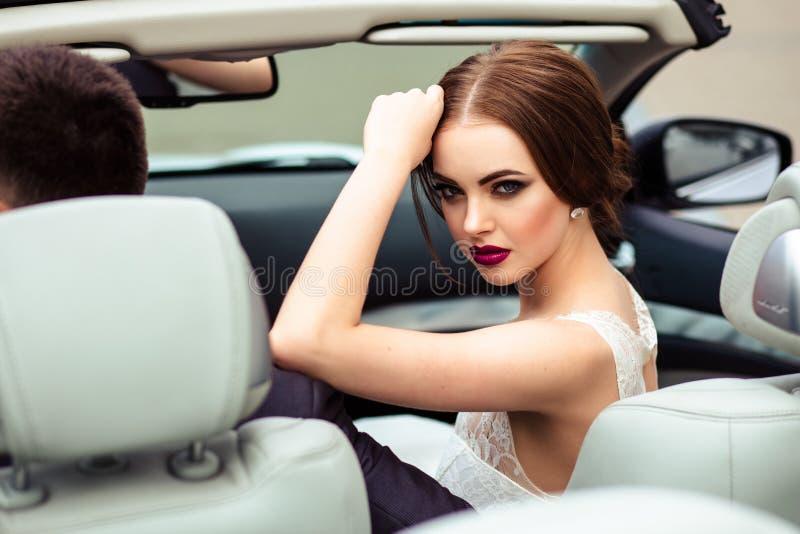 Πανέμορφη νύφη με τη μόδα makeup και hairstyle σε ένα γαμήλιο φόρεμα πολυτέλειας με τον όμορφο νεόνυμφο κοντά στο άσπρο αυτοκίνητ στοκ εικόνα