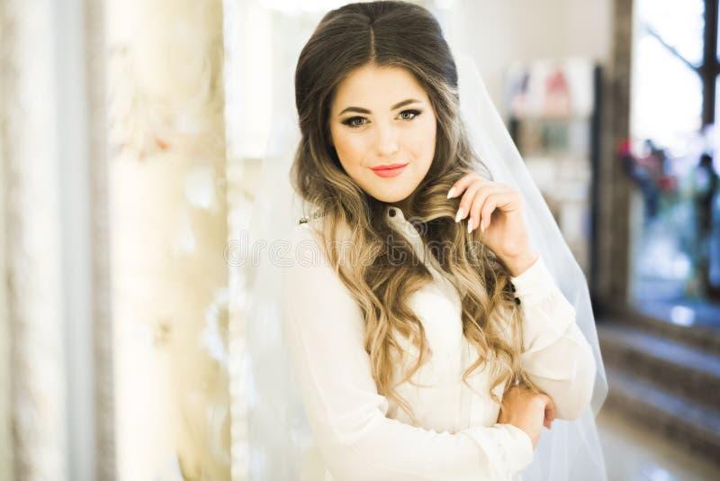 Πανέμορφη νύφη στην τήβεννο που θέτει και που προετοιμάζεται για το πρόσωπο γαμήλιας τελετής σε ένα δωμάτιο στοκ φωτογραφία